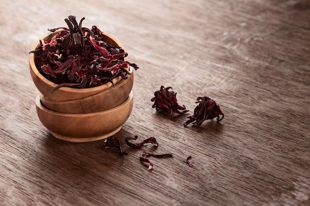 Hibiscus (roselle, karkade) droge bloemen in bowles op houten achtergrond.