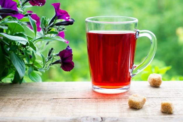 Hibiscus thee in een glazen beker op een houten tafel. plakjes rietsuiker bij een kopje.