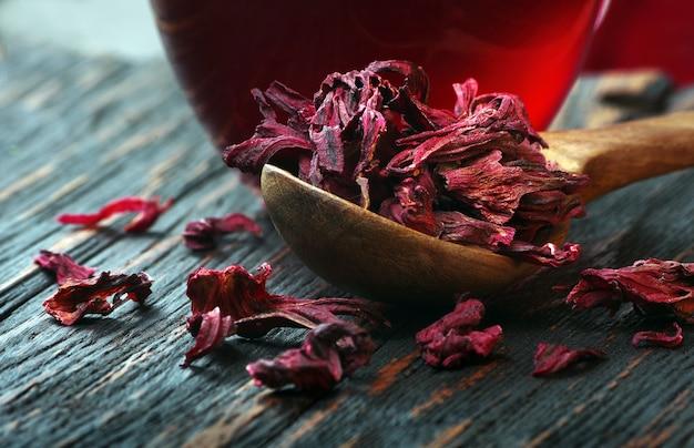 Hibiscusthee. droge hibiscusbloemblaadjes in een houten lepel op tafel. vitaminedrank bij griep en verkoudheid