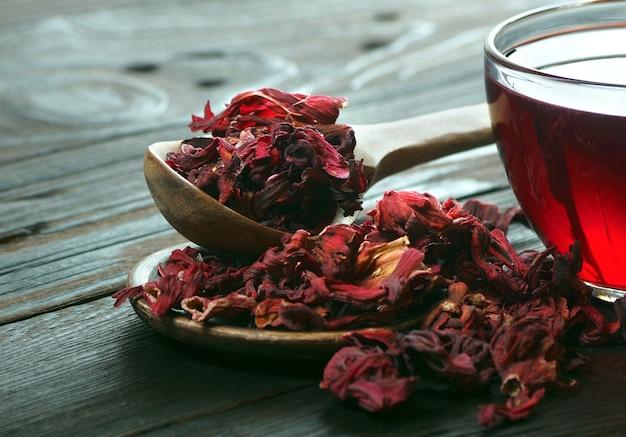 Hibiscusthee hibiscusthee in een houten lepel en een kopje verse hibiscusthee vitaminethee bij verkoudheid en griep
