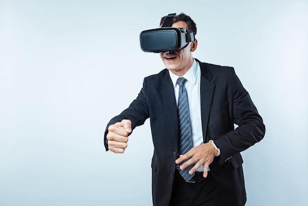 Hier ben je. volwassen man van zaken probeert te ontspannen na een zeer zware dag op kantoor en iemand te betrappen tijdens het spelen van virtual reality-spellen op de achtergrond.