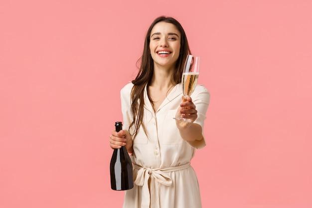 Hier drinken. de romantische tedere jonge donkerbruine vrouw opende flessenchampagne die lacht en glimlachend glas geeft aan vriendin, stelt voor om samen speciale gelegenheid, roze muur te vieren
