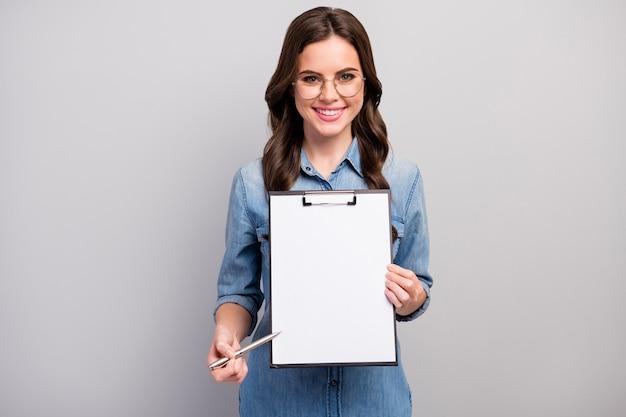 Hier! foto van mooie golvende zakelijke dame houd klembord met contract ruimte voor het aanmelden details slijtage specs casual jeans denim overhemd geïsoleerde grijze kleur