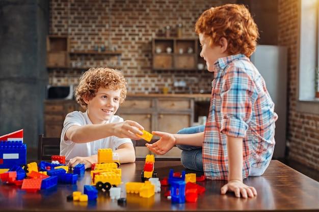 Hier is het stuk dat je nodig hebt. selectieve focus op een glimlachende jongen met krullend haar die naar zijn broertje kijkt, zittend op een houten tafel en hem een felgele plastic steen geeft