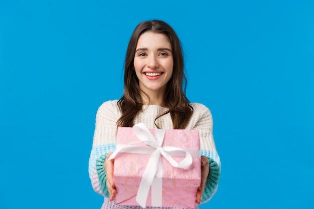 Hier is het voor jou. vrolijke, mooie en vriendelijke glimlachende donkerbruine vrouw die handen uitbreidt en heden geeft, feliciteert met verjaardag, gelukkige vakantie, gemaakte gift, die zich blauw bevindt