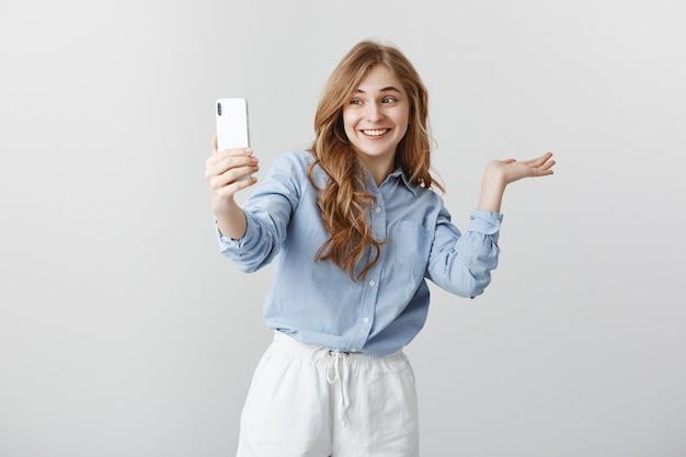 Hier is mijn kamer. portret van opgewonden gelukkig knappe vrouw in blauwe blouse die rond terwijl videochatten via smartphone, breed lacht, regisseert naar kopie ruimte over grijze muur
