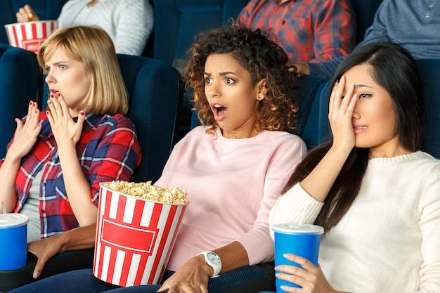 Hier komt het enge deel. portret van drie mooie vrouwelijke vrienden schreeuwen en kijken bang tijdens het kijken naar een film samen in de bioscoop