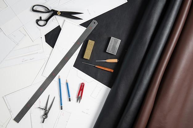 Hier zijn lederen schaar meetlint en tekeningen op de tafel