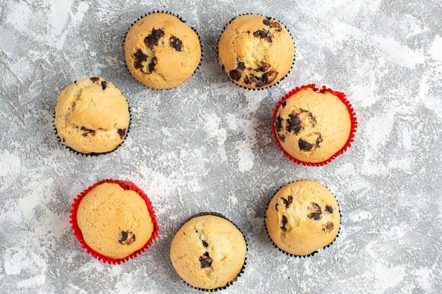Hierboven heerlijke kleine cupcakes met chocolade op ijsoppervlak