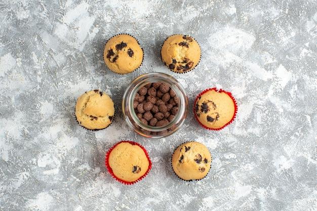 Hierboven heerlijke kleine cupcakes rond chocoladekoekjes in een glazen pot op ijsoppervlak