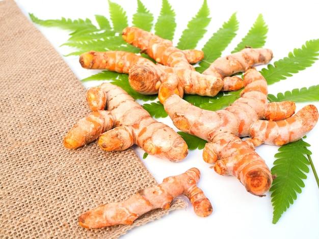 Hierboven van thaise kruidgroente met kurkumawortel op varenblad en jute op witte oppervlakte wordt geïsoleerd die.