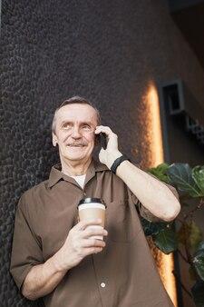 Hieronder een beeld van een zelfverzekerde senior blanke man in een bruin shirt, leunend op een zwarte stenen muur en communicerend via de mobiele telefoon