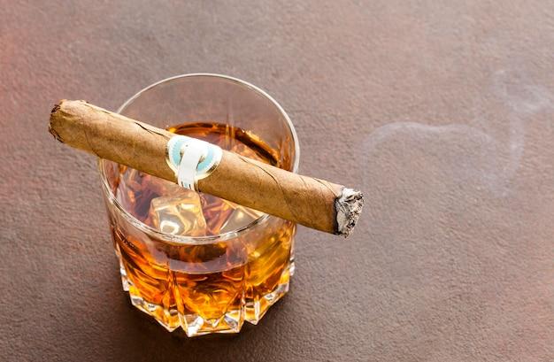 High-angle whiskyglas met ijs en sigaar