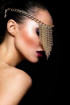 High fashion look.glamor close-up portret van mooie sexy blanke jonge vrouw model met kleurrijke lippen, lichte make-up, met perfecte schone huid met sieraden op oog geïsoleerd op zwart