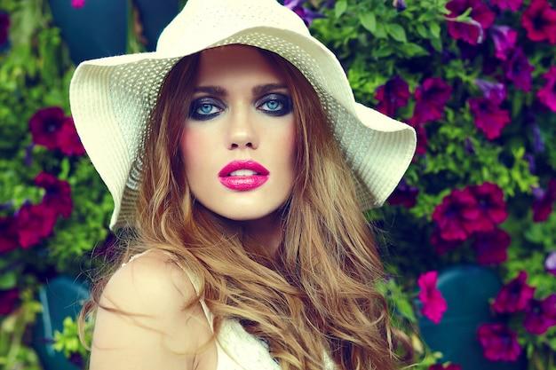 High fashion look.glamor close-up portret van mooie sexy stijlvolle blonde jonge vrouw model met lichte make-up en roze lippen met perfecte schone huid in hoed in de buurt van zomerbloemen