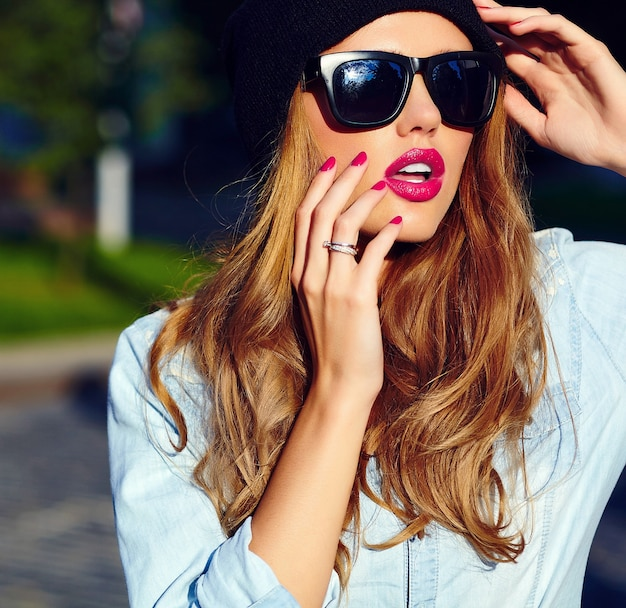 High fashion look.glamor levensstijl blonde vrouw meisje model in casual jeans broek doek buiten in de straat in zwarte pet in glazen