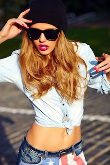 High fashion look.glamor lifestyle blond vrouw meisje model in casual jeans shorts doek buiten in de straat in zwart pet in glazen