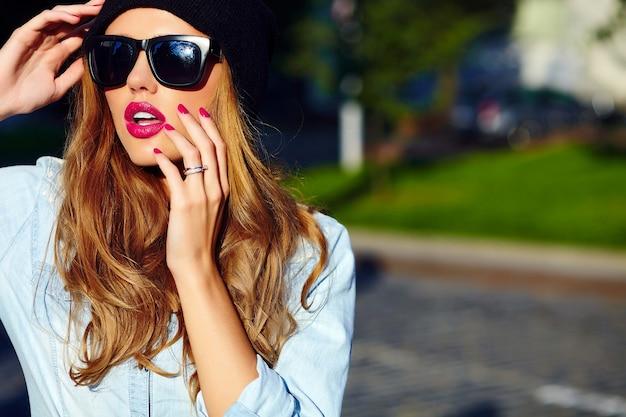 High fashion look.glamor lifestyle blond vrouw meisje model in casual jeans shorts doek buiten in de straat in zwart pet in glazen