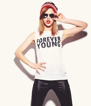 High fashion look.glamor stijlvolle mooie jonge vrouw model met rode lippen in hipster doek in zonnebril in kleurrijke muts