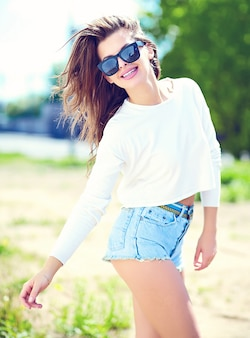 High fashion look.glamor stijlvolle sexy lachende mooie sensuele jonge vrouw model in zomer heldere hipster doek in jeans broek in de straat