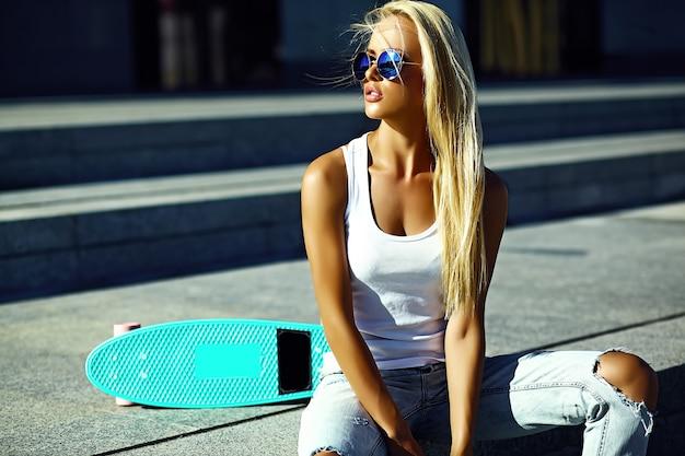 High fashion look.glamor stijlvolle sexy mooie jonge blonde model meisje in zomer heldere casual hipster kleding met skateboard zittend in de straat