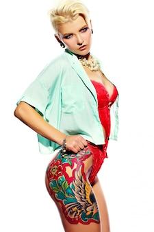 High fashion look. glamour close-up portret van mooie sexy hete stijlvolle blonde jonge vrouw model met kort haar lichte make-up met tatoeage in rode lingerie