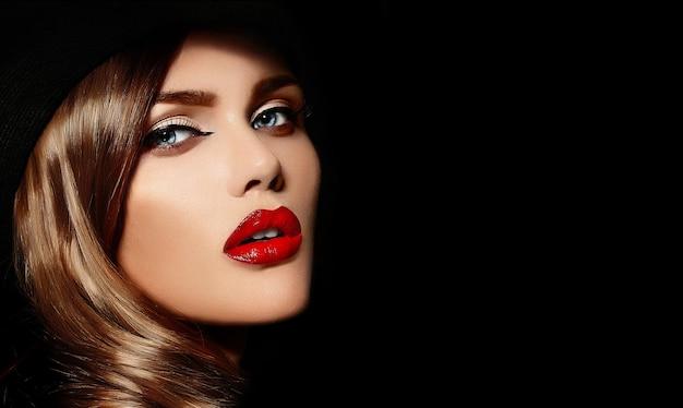 High fashion look. glamour close-up portret van mooie sexy stijlvolle blanke jonge vrouw model met lichte make-up, met rode lippen, met een perfecte schone huid in grote zwarte hoed