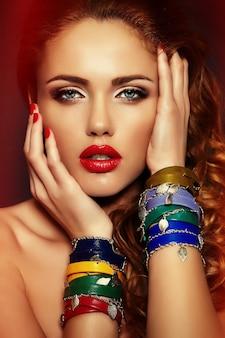 High fashion look. glamour close-up portret van mooie sexy stijlvolle blonde blanke jonge vrouw model met lichte make-up, met rode lippen, met een perfecte schone huid met kleurrijke accessoires