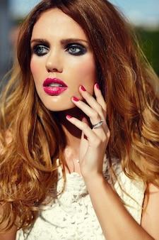 High fashion look. glamour close-up portret van mooie sexy stijlvolle blonde jonge vrouw model met lichte make-up en roze lippen met perfecte schone huid in witte zomerjurk in de stad