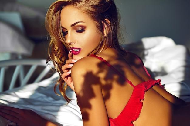 High fashion look. glamour close-up portret van mooie sexy stijlvolle jonge vrouw model liggend op wit bed met lichte make-up, met rode lippen, met een perfecte schone huid in rode lingerie