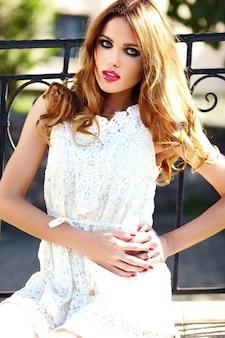 High fashion look. glamour close-up portret van mooie stijlvolle blonde jonge vrouw model met lichte make-up en roze lippen met perfecte schone huid in witte zomerjurk in de stad