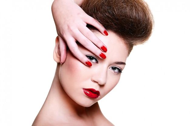 High fashion look.glamour close-up portret van sexy brunette blanke jonge vrouwelijke vrouw met lichte make-up met rode lippen en rode heldere manicure