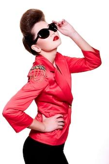 High fashion look. glamour close-up portret van sexy brunette blanke jonge vrouwelijke vrouw met lichte make-up met rode lippen in fel roze jas in zonnebril