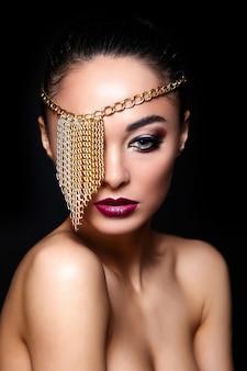 High fashion look. glamour mode portret van mooie sexy brunette meisje met lichte make-up en gouden accessoires op oog