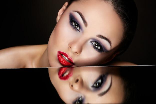 High fashion look.glamour mode portret van mooie sexy brunette meisje met lichte make-up en rode lippen en haar spiegelbeeld in spiegel tafel op donker