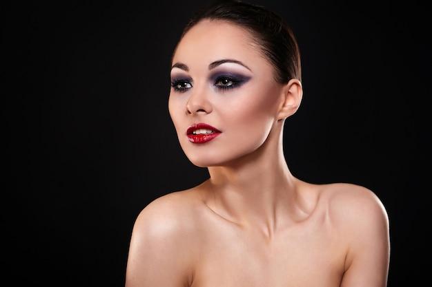 High fashion look.glamour mode portret van mooie sexy brunette meisje met lichte make-up en rode lippen op donker
