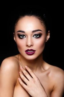 High fashion look. glamour mode portret van mooie sexy brunette meisje met lichte make-up en rode lippen op donker