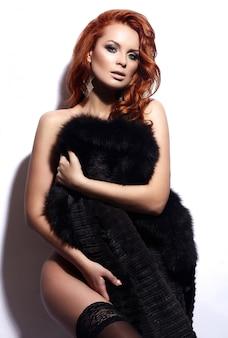 High fashion look. glamour portret van mooie sexy roodharige stijlvolle naakt blanke jonge vrouw model met lichte make-up, met perfect schoon in lingerie in bontjas