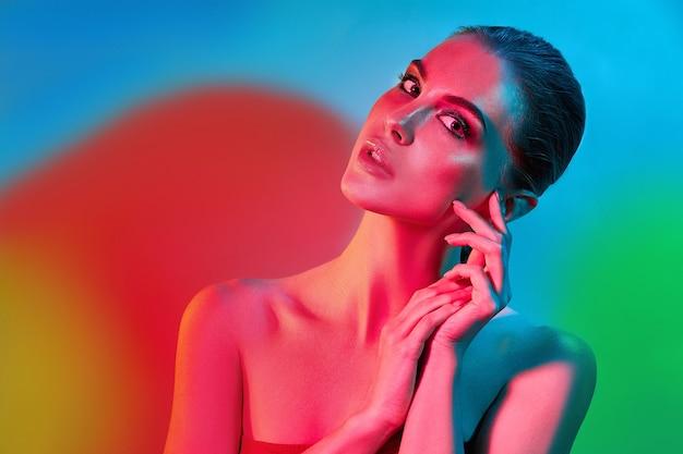 High fashion model vrouw in kleurrijke felle lichten poseren in studio, portret van mooi sexy meisje met trendy make-up en manicure. art design, kleurrijke make-up. over kleurrijke levendige achtergrond.
