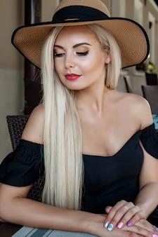 High fashion portret van een sierlijke vrouw in een elegante strooien hoed en jurk die in een café aan een tafel zit