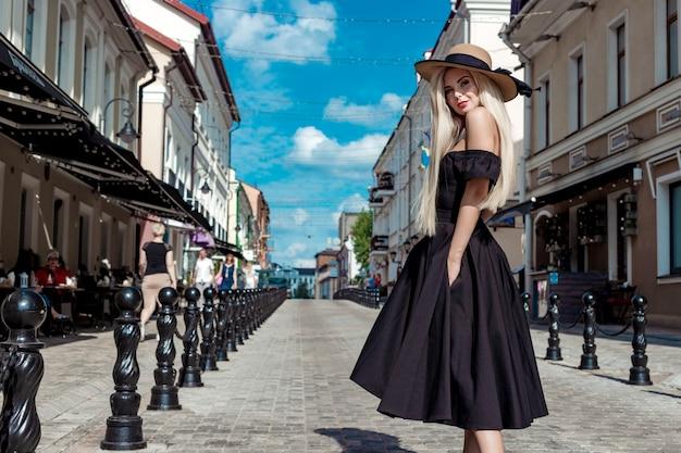 High fashion portret van een sierlijke vrouw in een elegante strooien hoed en jurk die langs een straat in de stad loopt