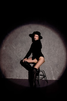 High fashion portret van elegante vrouw in zwarte hoed en romper. studio opname.