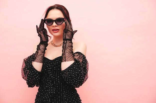 High fashion portret van jonge mooie brunette vrouw met mooie trendy zomerse polka-dot jurk en handschoenen