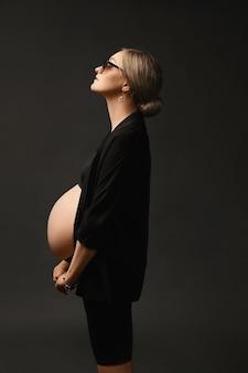 High fashioned jonge zwangere vrouw in een modieuze zwarte outfit met blote buik staat zijwaarts en kijkt weg naar de donkere achtergrond, geïsoleerd