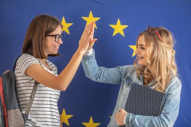 High-five door twee vrouwelijke studenten met de vlag van de europese unie op de achtergrond.