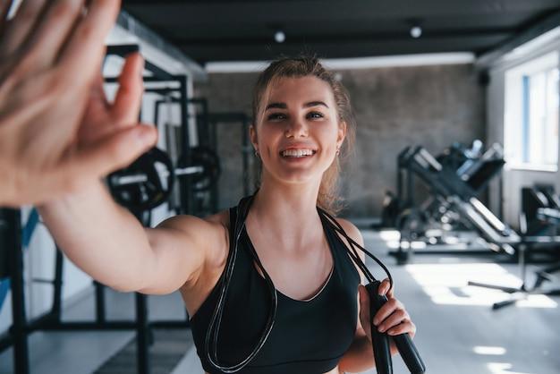 High-five geven. prachtige blonde vrouw in de sportschool tijdens haar weekend