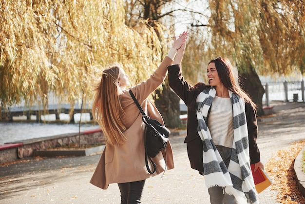 High five. twee jonge vrienden ontmoeten elkaar na het studeren graag in het park