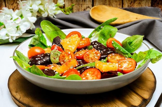 High view van exquise salade van rode biet, sinaasappel, cherrytomaat en rucola met olijfolie
