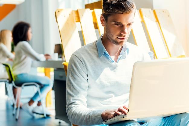 Hij is altijd hard aan het werk. geconcentreerde jonge man aan het werk op laptop terwijl zijn collega's op de achtergrond werken