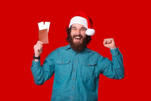 Hij is de winnaar van een reis voor twee. bebaarde man is opgewonden en houdt zijn paspoort met kaartjes vast.